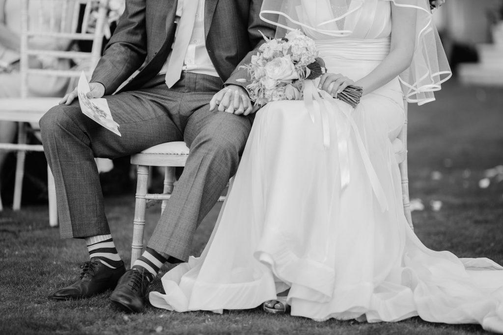 Bruidpaar (bruid en bruidegom) buiten op stoeltjes, hoofden niet de zien